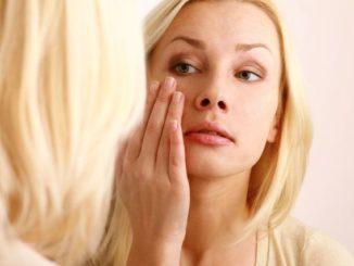 Женщина разглядывает кожу под глазами