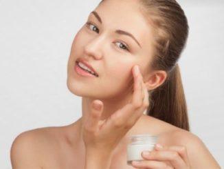 Женщина мажет лицо кремом