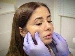 Врач осматривает щеки пациентки