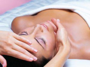 Женщине делают массаж лица