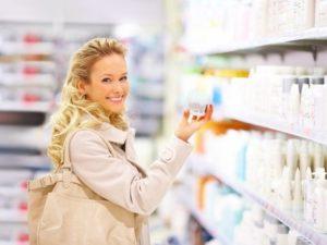Женщина в магазине выбирает крем