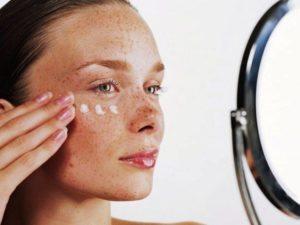 Женщина с веснушками смотрит в зеркало