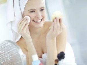 Женцщина с ватным диском и средствами для кожи