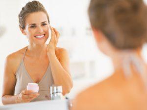 Женщина смотрится в зеркало и мажет лицо