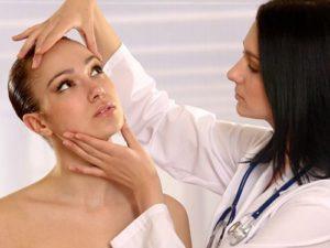 Врач осматривает лицо пациентки