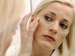 женщина разглядывает лицо в зеркало