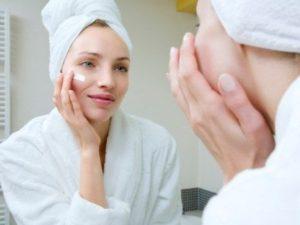 Нанесение крема на лицо перед зеркалом